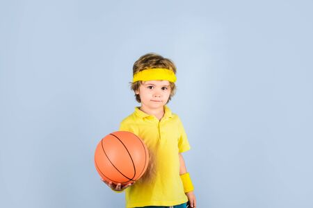 Basketball player in sportswear. Sport active. Hobby sport concept. Kid holds basketball. Sporty boy with ball. Sport, fitness, healthy lifestyle. Sport for children. Kid playing with basketball