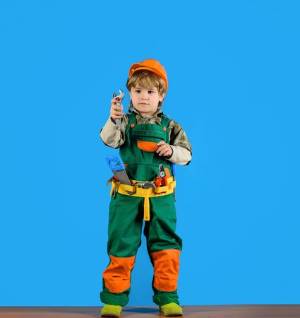Little kid boy in builder uniform with wrench. Tools for building. Kid repairman with tool belt. Work with tools. Repair. Kid boy as builder or repairer. Builder boy in helmet and tools. Child game Archivio Fotografico