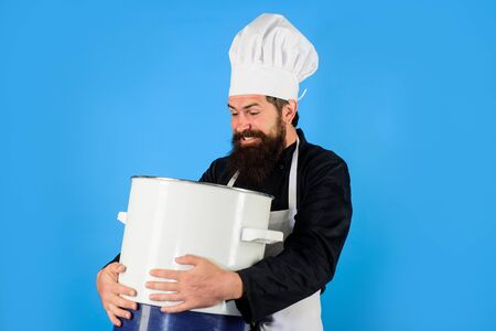 Handsome male chef with saucepan. Chef man in hat holds pan. Man in chef uniform with saucepan. Bearded man cook in kitchen. Healthy food cooking. Chef cooking tasty dish in kitchen. Kitchen utensils