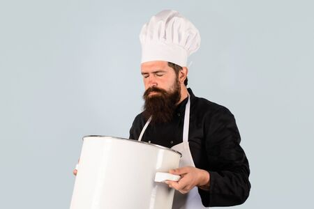 Chef with big casserole or saucepan. Professional cookery concept. Man with beard hold kitchenware. Cooking process concept. Kitchen tool. Utensil. Male cook in uniform. Cook in white apron holds pot Banque d'images