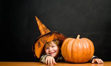 Otoño. Cocina del día de acción de gracias. Chico lindo niño con sombrero de bruja con calabaza de halloween apuntando hacia ti. Truco o trato. Feliz Halloween. Fiesta de Halloween. Disfraz de bruja. 31 de octubre. Chico con calabaza