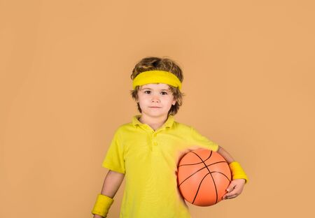 Sport active. Kid holds basketball. Sporty boy with ball. Boy in sportswear. Hobby sport concept. Sport, fitness, healthy lifestyle. Sport for children. Basketball player. Kid playing with basketball