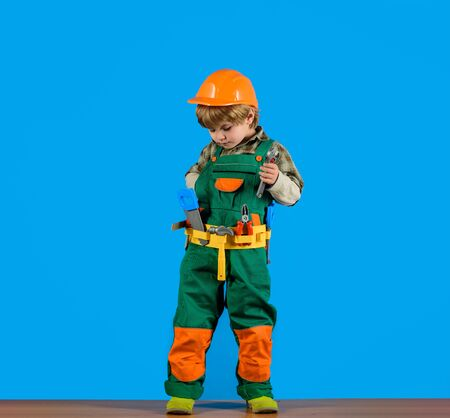 Little boy in helmet and tools. Kid as construction worker. Little boy plays construction worker. Builder. Little repairman. Child game. Tools for building. Little boy in builders uniform with tools Фото со стока