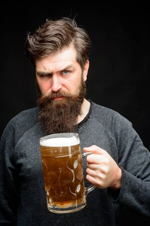 Bearded drunk hipster male holds craft beer. Stylish man with beard holds mug of beer. Bad habits. Drinks, alcohol, leisure and people concept. Bearded man drinking beer from glass at bar or pub Фото со стока