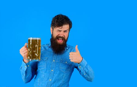 Winking man holds beer shows thumb up. Barman. Beer pub and bar. Bearded man holds glass with delicious ale. Craft beer at restaurant. Oktoberfest festival. Man tasting draft beer. Stylish man at pub