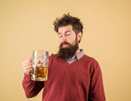 Bad habits. Stylish man with beard holds mug of beer. Drinks, alcohol, leisure and people concept. Bearded man drinking beer from glass at bar or pub. Bearded drunk hipster male holds craft beer