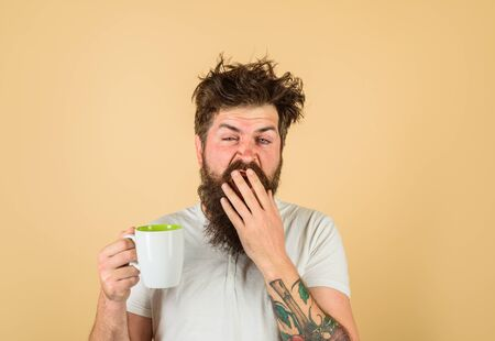 Sleepy man holds cup of coffee. Yawning man holds mug with hot drink.Man with cup of fresh coffee. Tired guy hold coffee mug. Morning refreshment. Man with sleepy face try to awake with cup of coffee