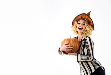 Witch magic. Jack-o-lantern. Party and traditional food. Magic hat. Halloween woman with happy face. Woman in witch hat holds pumpkin. Girl with orange pumpkin. Happy woman in witch halloween costume