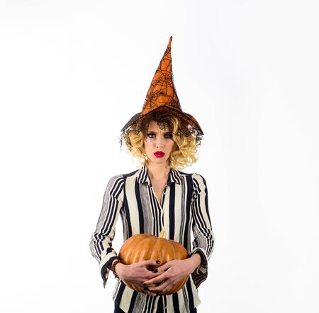 Halloween party. Traditional food. Sensual girl in witch hat with pumpkin. Halloween party. Costumes and witch hats. Advertisement Halloween concept. Woman in Halloween costume with orange witch hat