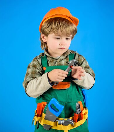 Little boy in helmet and tools. Builder. Little repairman. Child game. Kid as construction worker. Little boy plays construction worker. Tools for building. Little boy in builders uniform with tools