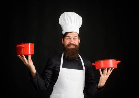 Male chef, cook, baker in uniform holds saucepan in hands. Cooking, food, profession. Professional chef man in cook hat. Chief man in white apron with pots. Bearded man cook wear chef hat and uniform