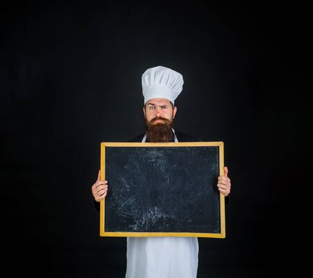 Chef. Empty menu chalkboard with copy space for text. Male chef, cook or baker with blank board. Man cook showing empty menu chalkboard with copy space. Serious chef holds blackboard. advertisement