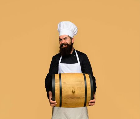 Celebration oktoberfest festival. Bearded cook with wooden barrel of beer. Wooden barrel of beer. Beer in Germany. Barman. Equipment for preparate of beer. Brewery for maturing alcohol. Homemade wine