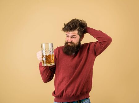 Bad habits. Bearded man drinking beer from glass at bar or pub. Bearded drunk hipster male holds craft beer. Stylish man with beard holds mug of beer. Drinks, alcohol, leisure and people concept