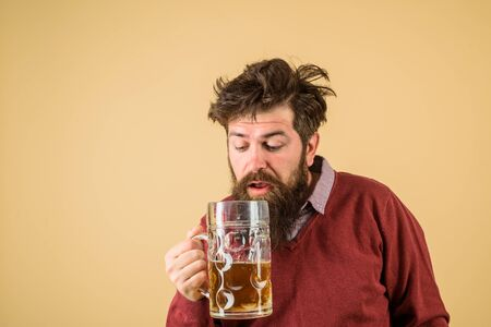 Bearded drunk hipster male holds craft beer. Bearded man drinking beer from glass at bar or pub. Drinks, alcohol, leisure and people concept. Bad habits. Stylish man with beard holds mug of beer Imagens