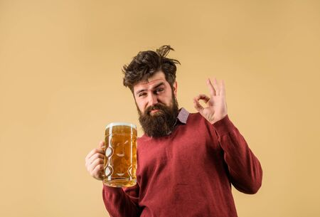 Bearded drunk hipster male holds craft beer. Bad habits. Bearded man drinking beer from glass shows ok sign. Drinks, alcohol, leisure and people concept. Stylish man with beard holds mug of beer