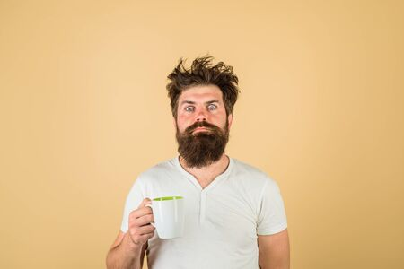 Sleepy guy with cup of tea or coffee. Morning with coffee or milk. Man with sleepy face try to awake with cup of coffee. Sleepy man with beard holds mug in hand. Morning coffee. Breakfast concept