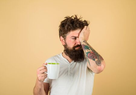 Tired sleepy man with beverage in cup. Morning refreshment and drink. Breakfast concept. Handsome bearded young man drinking coffee or tea. Bearded man with white coffee cup. Refreshment and energy