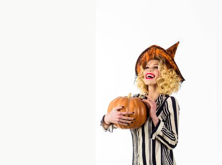 Happy witch with Pumpkin. Happy Halloween Quotes and Sayings. Girl with orange pumpkin. Holidays. Emotional woman in witch halloween costume with jack o lantern. Halloween party. Traditional food