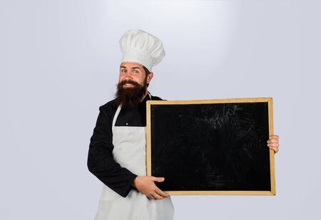 Advertising chef menu. Restaurant chef show empty chalkboard. Blank chalkboard with copy space for text. Male chef, cook or baker with blank board. Bearded chef holds blackboard. Business lunch menu