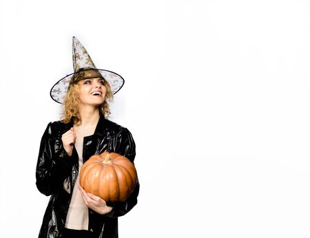Happy Halloween party. Girl with orange pumpkin. Traditional food. Halloween. Smiling woman in witch halloween costume with jack o lantern. Girl witch with Pumpkin. Happy Halloween Quotes and Sayings