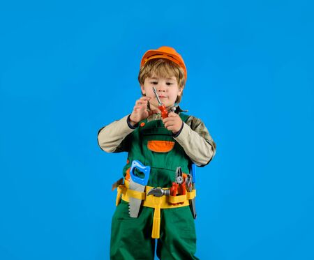 Little boy in builders uniform with screwdriver. Tools for building. Builder boy in helmet and tools. Little repairman with tool belt. Child game. Work with tools. Repair. Boy as builder or repairer