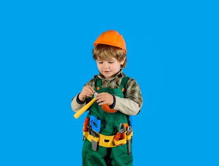Little repairman with tool belt. Little boy in builder's uniform with hammer. Tools for building. Builder boy in helmet and tools. Child game. Work with tools. Repair. Kid boy as builder or repairer