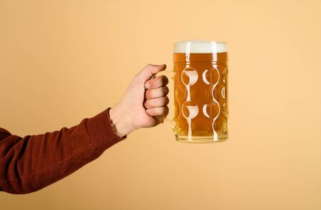Oktoberfest. Man hand holds glass of draft lager beer. Fresh cold beer in glass in hand. Beer pub. Bavarian service. Leisure, drinks, degustation, people and holidays concept. Beer in mug with foam Stockfoto