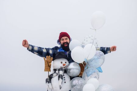 Happy holiday. Bearded man with snowman. Handmade snowman in hat, scarf, gloves with air balloons. Christmas, New Year, birthday concept. Wintertime. Winter fashion. Winter man standing near snowman