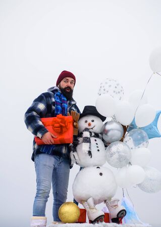 Happy holiday. Christmas, New Year, birthday concept. Bearded man with snowman holds gift. Handmade snowman in hat, scarf and gloves with air balloons. Winter fashion. Snowman in cap, scarf in winter
