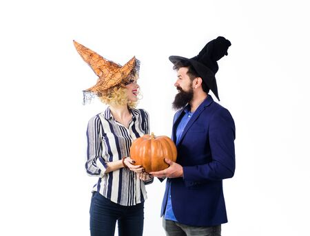 Celebration and party concept. 31 october. Magic for Halloween. Halloween couple in witches hats with pumpkin. Preparation Halloween holidays. Jack o lantern. Young people dressed at Halloween party