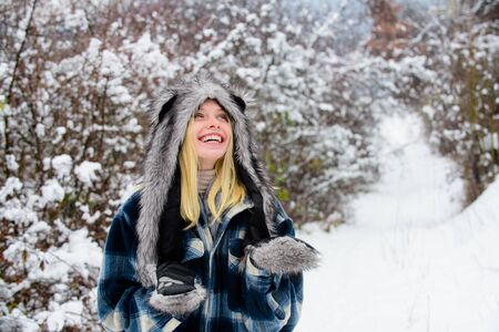 Happy girl playing snow winter day. Winter holidays. Beautiful woman in warm coat, fur hat and mittens. Cold winter weather. Christmas girl in warm clothing in winter park. Fashion girl in wintertime