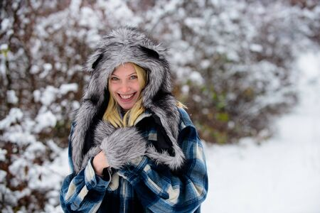 Cold winter weather. Happy girl playing snow winter day. Winter holidays. Beautiful woman in warm coat, fur hat and mittens. Christmas girl in warm clothing in winter park. Fashion girl in wintertime