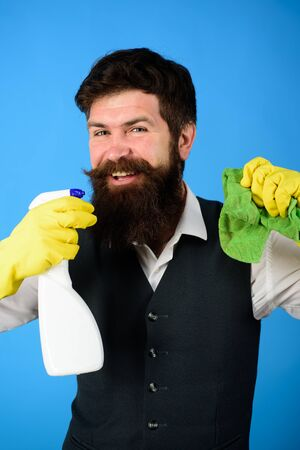 Professional cleaning man in uniform. Bearded man in uniform, rubber gloves with cleaning products. Domestic service cleaner man with rag and cleaner spray. Male janitor with cleaning equipments