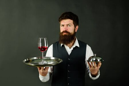 Waiter holds tray with wine and metal cloche lid cover. Handsome man waiter in uniform at restaurant. First class service concept. Best service. Professional catering service. Butler concept. Waiter Stockfoto