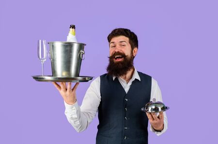 Waiter. Restaurant serving. Handsome waiter with serving tray and wine cooler. Waiter in restaurant carrying metal cloche lid cover and ice bucket with bottle, glass. Professional waiter in uniform