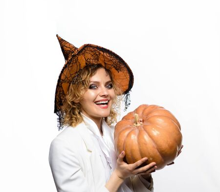 Witch. Smiling woman in witches costume. Halloween witch with bright make-up. Beautiful woman in witch hat holds pumpkin. Trick or treat. Halloween witch with carved Pumpkin. Halloween party girl Stockfoto