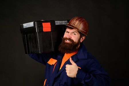 Tools for repair. Builder man carrying tool box giving thumbs up. Repairman in overall hold toolbox. Man with tool box. Builder in protective helmet with toolbox. Repair. Handyman concept. Repair kit