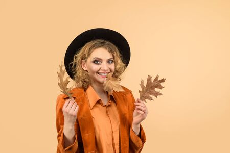 Autumn girl in black hat. Happy woman with autumn leaves in orange jacket. Woman autumn fashion. Fashionable woman with autumn leaves in hand. Fall. October. Beautiful model girl with autumnal leaves