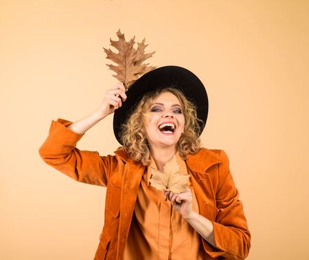 Woman autumn fashion. Autumn girl in black hat. Happy woman with autumn leaves in orange jacket. Fashionable woman with autumn leaves in hand. Fall. October. Beautiful model girl with autumnal leaves