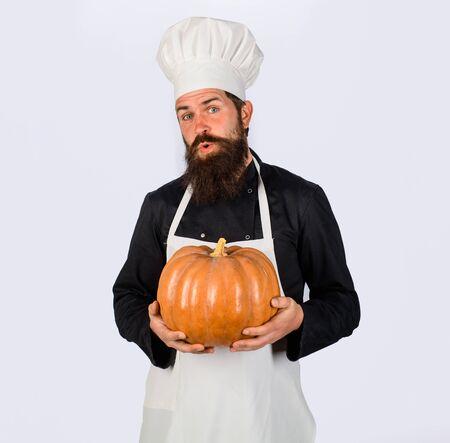 Autumn vegetables. Big pumpkin for Halloween. Fresh Pumpkin. Harvest pumpkin. Bearded cook in chef hat with pumpkin. Diet food. Healthy vegetarian eating. Farm market. Chef preparing meal in kitchen