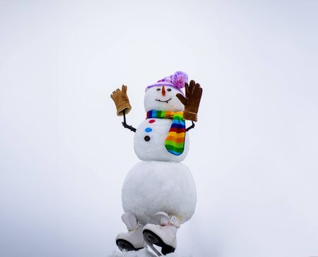 Christmas snowman in hat, scarf, gloves with ice skating. Merry christmas and happy new year greeting card. Happy snowman in winter landscape. Christmas and winter fashion. Happy holiday celebration