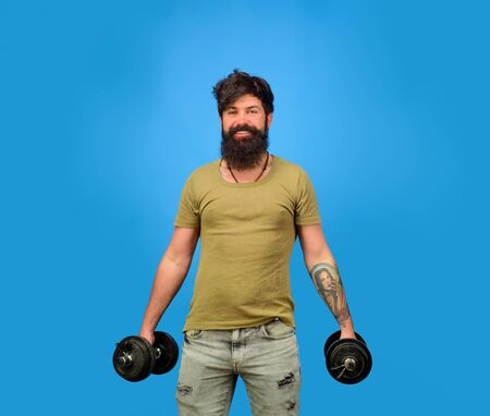 Athletic man doing exercise with dumbbells. Handsome man lifting dumbbells at gym. Sporty man with dumbbells. Strength and motivation. Athletic guy with dumbbells. Strong athletic man fitness model