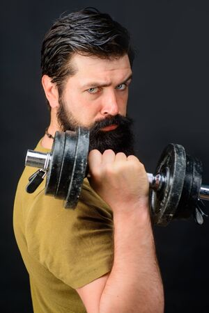 Bearded man with dumbbell during exercise. Strong handsome sport man making weightlifting. Muscular fitness model raising dumbbell. Man with dumbbell in gym. Bearded man working out with dumbbell Stockfoto