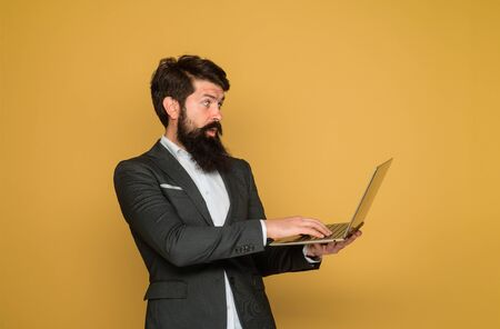 Technology, networking and internet. Surprised man with laptop computer at office. Business man with computer at workplace. Businessman works with laptop. Businessman working with notebook in office