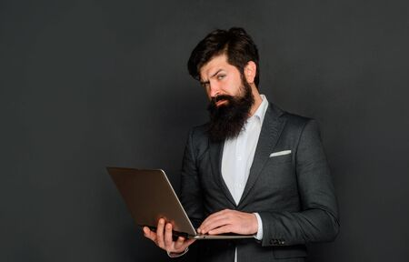 Work at office. Serious man with laptop computer. Businessman works with notebook in office. Businessman with computer at workplace. Businessman works with laptop. Technology, networking and internet