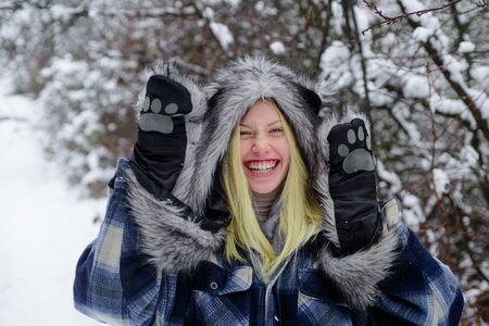 Cold winter weather. Christmas girl in warm clothing in winter park. Happy girl playing snow winter day. Fashion girl in wintertime. Winter holidays. Beautiful woman in warm coat, fur hat and mittens
