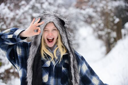 Winking woman in warm coat, hat shows sign ok. Cold winter weather. Fashion girl in wintertime. Christmas girl in warm clothing in winter park. Smiling girl showing okay gesture. Winking winter girl