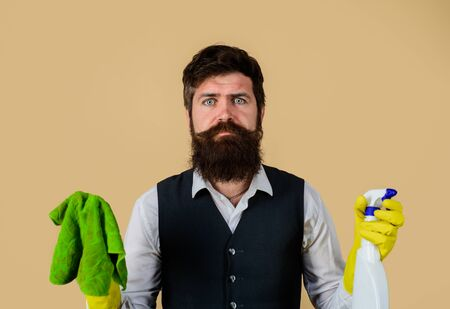 Bearded man in uniform, rubber gloves with cleaning products. Domestic service cleaner man with rag and cleaner spray. Male janitor with cleaning equipments. Professional cleaning man in uniform