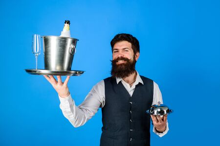 Handsome waiter with serving tray and wine cooler. Waiter in restaurant carrying metal cloche lid cover and ice bucket with bottle, glass. Waiter. Professional waiter in uniform. Restaurant serving Stockfoto